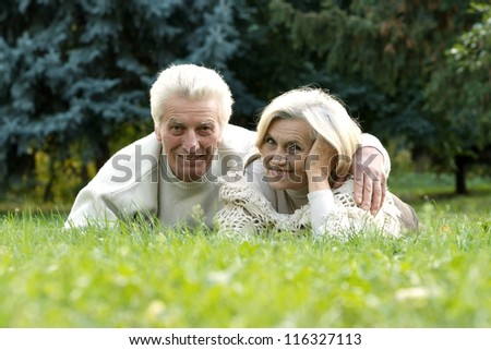 portrait of a nice mature couple lying on the autumn