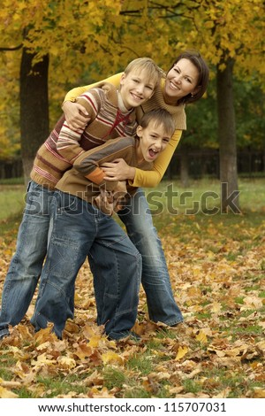 portrait of a nice mom and her children on autumn background