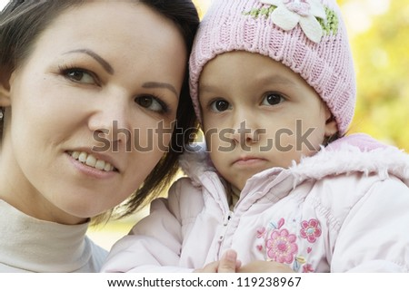 portrait of a nice mother and a little girl in the autumn
