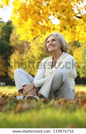 portrait of a nice old woman sitting in the autumn park
