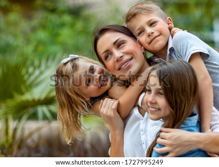 Portrait of a nice young mother with pleasure spending time with her three precious kids in the spring park, everyone hugging their lovely mom, having fun together, happy big family enjoying life