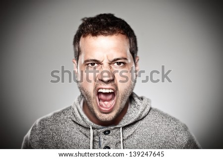 Portrait of a normal man looking furious./ Young man screaming over grey background. #139247645