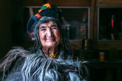 Portrait of a old woman in typical tibetan clothes inside her house in Ladakh, Kashmir, India.