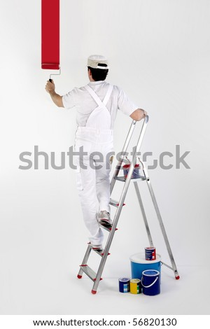 Portrait of a painter painting a white wall in red
