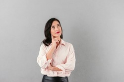 Portrait of a pensive businesswoman standing and looking away at copy space isolated over gray background