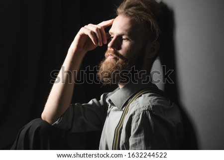 Portrait of a pensive handsome young man, on an isolated black background.
