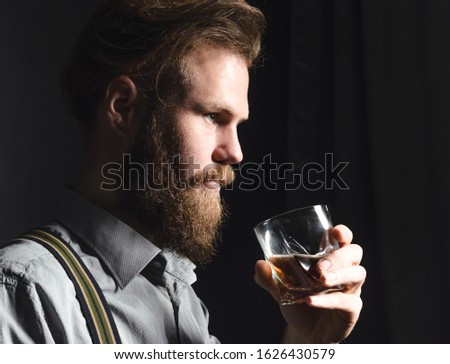 Portrait of a pensive handsome young man, with a glass of alcohol in his hands.