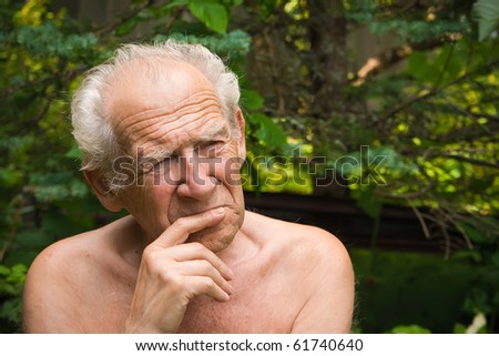 portrait of a pensive senior man holding his hand near his face