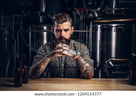Portrait of a pensive tattooed hipster male with stylish beard and hair in the shirt in indie brewery.   #1204514377