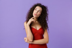 Portrait of a pensive woman with dark curly hair wearing red dress isolated over violet background, looking away