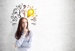 Portrait of a pensive young woman with long brown hair wearing a blue shirt and standing near a concrete wall with question marks and a yellow light bulb drawn on it. Mock up