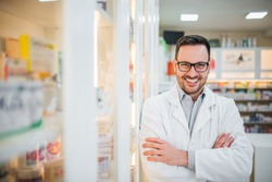 Portrait of a pharmacist at drugstore, smiling at camera.