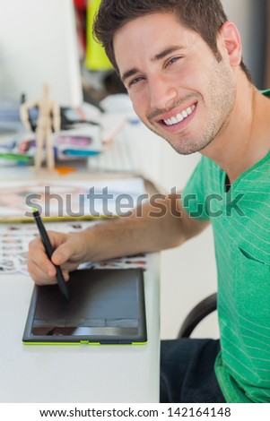 Portrait of a photo editor working on graphics tablet at his desk