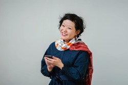 Portrait of a photogenic middle-aged Chinese Asian woman in a blue dress and colorful scarf texting on her smartphone. She is smiling and is happy as she texts and has short hair.