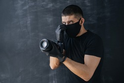 Portrait of a photographer, a man in a black medical mask and gloves, holding a professional digital camera and looking into the frame. Self-isolation and quarantine. Protection.
