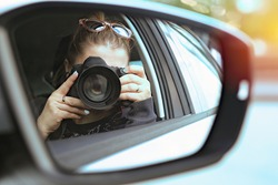 Portrait of a photographer covered her face with a camera while sitting in a car from a window photographing people on the street. At work. Lens close-up. Photo in the mirror of a car.  Report Concep