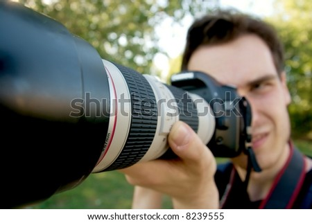 Portrait of a photographer taking pictures with a telephoto lens