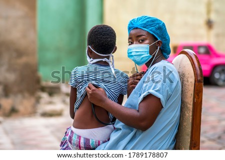 portrait of a physician wearing face mask for protection and listening to the back of a kid with mask tied behind her,sitting on physician lap-concept on health care in coronavirus pandemic