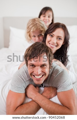 Portrait of a playful family lying on each other in a bedroom