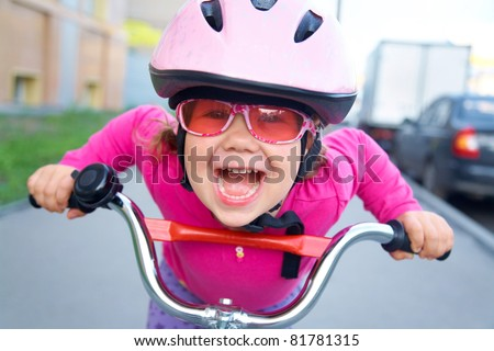 Portrait of a playful funny girl in a pink safety helmet on her bike
