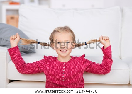 Portrait of a playful girl pulling her pigtails in the living room at home