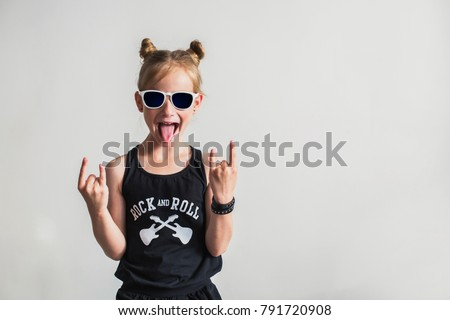 Portrait of a playful little girl with tongue out. Cute little girl making a rock-n-roll sign. #791720908