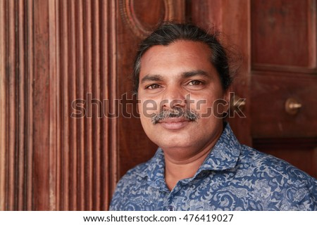 Portrait of a pleasant looking man of Indian origin against a wooden background
