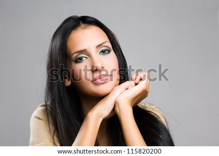 Portrait of a pondering beautiful young brunette woman.