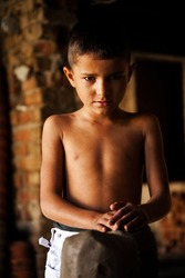 portrait of a poor little Indian boy in a workshop, child labor