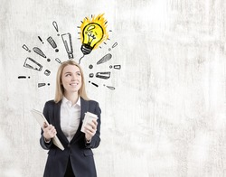 Portrait of a positive blond woman standing near a concrete wall with a light bulb drawing surrounded by exclamation marks on it. Mock up