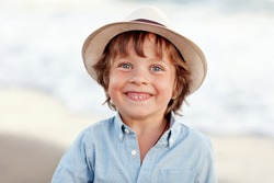 Portrait of a positive boy (4-5 years) in a hat on the beach on a summer day .Outdoor, close up.