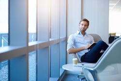 Portrait of a positive young businessman sitting in a modern corporate environment, looking at the camera while holding his diary, with gentle sunflare through the windows
