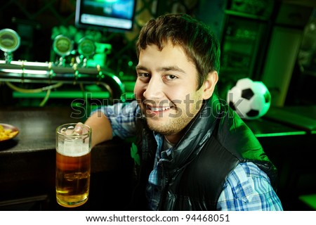 Portrait of a positive young man holding a mug of beer and looking at camera