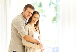 Portrait of a pregnant woman and husband looking at camera standing at home
