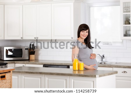Portrait of a pregnant woman at home drinking orange juice