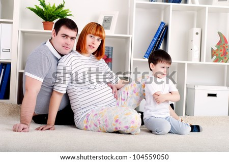 portrait of a pregnant woman, father and his son, at home
