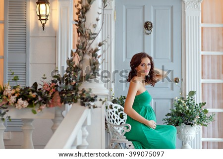 Portrait of a pregnant woman sensual brunette with bright eyes in green dress, the interiors of the studio in the spring #399075097