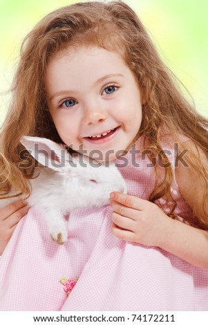 Portrait of a preschool girl holding white rabbit