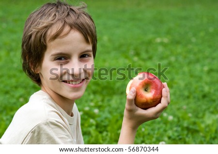 Portrait Of A Preteen Boy With A Apple In His Hand And Green Grass ...