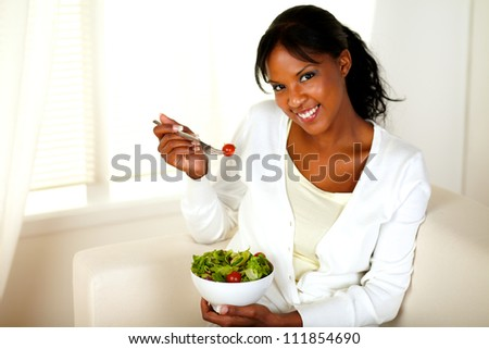 Portrait of a pretty and smiling girl eating a salad and looking at you at home indoor.