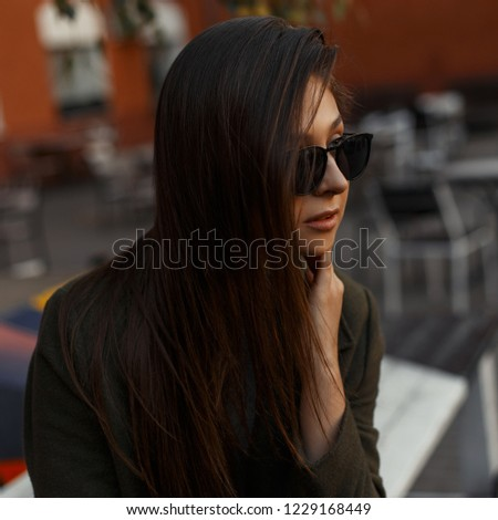 Portrait of a pretty attractive and young brunette girl in shiny black stylish glasses and trendy clothes. Fashionable woman. #1229168449