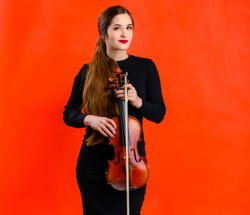 Portrait of a pretty brunette musician girl with a smile in a black dress on a red background holds a violin in her hands