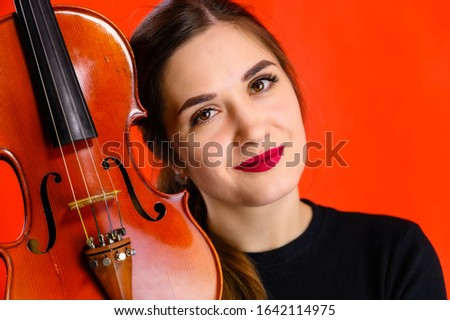 Portrait of a pretty brunette musician girl with a smile in a black dress on a red background holds a violin in her hands Сток-фото ©