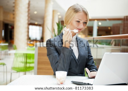 Portrait of a pretty businesswoman sitting at cafe with a laptop using wireless internet, having dessert after lunch