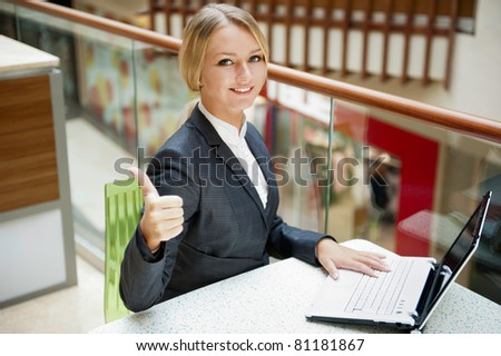 Portrait of a pretty businesswoman sitting at cafe with a laptop using wireless internet, thumbs up
