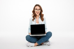 Portrait of a pretty casual girl showing blank screen laptop computer while sitting on a floor isolated over white background