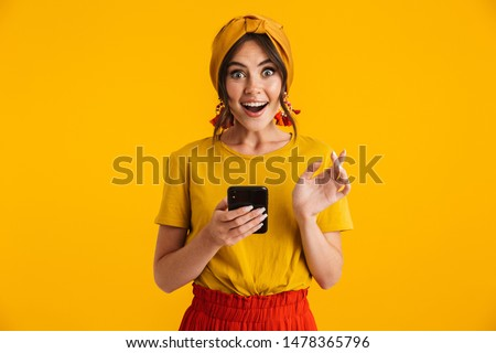 Portrait of a pretty cheerful young girl casually dressed standing isolated over yellow background, holding mobile phone