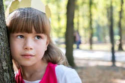 Portrait of a pretty child girl in a paper crown on her head leaning to a tree in summer park.
