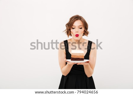 Portrait of a pretty girl holding plate with a piece of birthday cake and blowing a candle isolated over white background