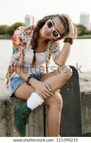 Portrait of a pretty girl with a skateboard, outdoors
